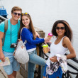 Multi-ethnic friends tourists with map and coffee cups near river in a city — Stock Photo #50513883