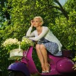 Beautiful blond woman sitting on a retro roller — Stock Photo