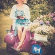 Beautiful blond woman sitting on a retro roller with a book — Stok fotoğraf