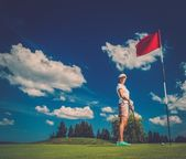 Young woman near hole with red flag on a golf club field  — Stock Photo