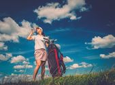 Young woman drinking water on a golf field  — Stock Photo
