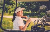 Young cheerful woman with bottle of water driving golf cart  — Stock Photo