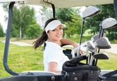 Young cheerful woman driving golf cart  — Stock Photo