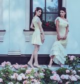 Tow women in dress near luxury building facade among roses  — Stock Photo