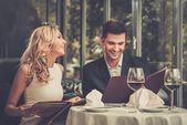 Cheerful couple with menu in a restaurant  — Stock Photo