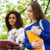 Multi ethnic girls students in a city park  — Stock Photo