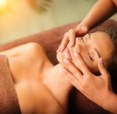 Young woman having face massage in a spa salon — Stock Photo