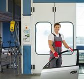 Cheerful serviceman with car door near paint booth in a car body workshop — Stock Photo