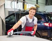 Young serviceman performing grinding with machine on a car bonnet in a workshop — Stock Photo