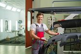 Serviceman with car bodykit ready for painting in a workshop — Stock Photo