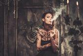 Smoking tattooed beautiful woman  in old spooky interior — Stock Photo