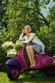 Belle femme blonde assise sur un rouleau rétro — Photo