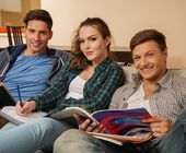 Three young students preparing for exams in apartment interior  — Stock Photo