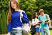 Beautiful young girl student in a city park on summer day  — Stock Photo