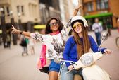 Multi ethnic girls on a scooter in european city — Stock Photo