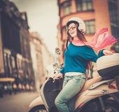 Young cheerful girl near scooter in in european city  — Stock Photo