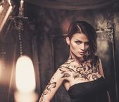 Tattooed beautiful woman in old spooky interior — Stock Photo