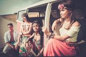 Multi-ethnic hippie friends with guitar on a road trip — Stock Photo