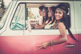 Multi-ethnic hippie friends in a minivan on a road trip — Stock Photo
