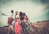 Multi-ethnic hippie friends with guitar in a wheat field  — Stock Photo
