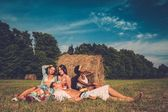 Multi-ethnic friends relaxing near stack in a field  — Stockfoto