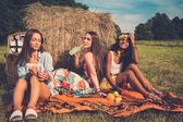 Multi-ethnic girls having picnic near stack on a field  — Foto de Stock