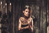 Smoking tattooed beautiful woman  in old spooky interior — Stock Photo