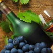 Bottle, glass of cognac and bunch of grapes — Stock Photo #13637222