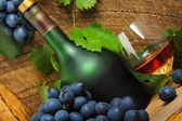 Bottle, glass of cognac and bunch of grapes — Stock Photo