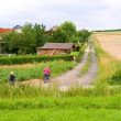Children by bicycles go on the field road — Stock Photo