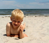 The boy lies on the sea beach — Stock Photo