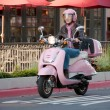 Lady biker zipping along on her pink sco — Stock Photo #1910041