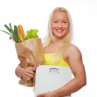 Portrait of smiling woman poing in studio with food — Stock Photo