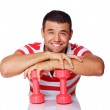 Portrait of smiling man posing in studio with dumbbells — Stock Photo #12397315