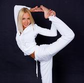 Portrait of smiling yoga trainer posing on black background — Stock Photo