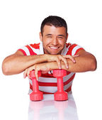 Portrait of smiling man posing in studio with dumbbells — Stock Photo