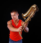 A young musician is swinging his saxophone — Stock Photo
