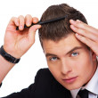 A young man with a comb - Stock Photo