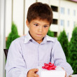 Portrait of handsome kid going to open gift - Stock Photo
