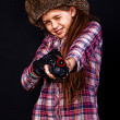 Portrait of beautiful girl posing in studio with gun in hat — Стоковая фотография
