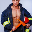Stock Photo: Portrait of handsome fireman posing on white background