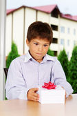 Portrait of handsome kid going to open gift — Stock Photo