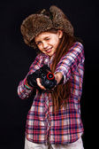 Portrait of beautiful girl posing in studio with gun in hat — Stock Photo