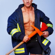 Stock Photo: Portrait of handsome man posing on black background in fireman c