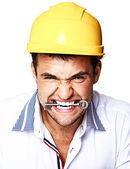 Portrait of handsome worker posing in studio with helmet and key — Stock Photo