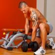 Handsome man with muscles lift a dumbbell — Stock Photo #20041569