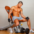 Stock Photo: Handsome man with muscles lift a dumbbell