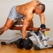 Handsome man with muscles lift a dumbbell — Stock Photo
