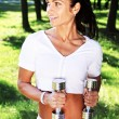 Gorgeous woman posing with the dumbbells in the park — Stock Photo