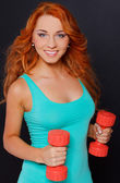 Woman posing with dumbbells on a dark background — Stock Photo